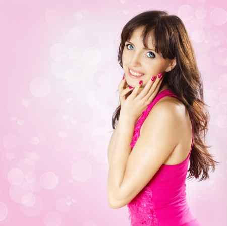 Beautiful smiling brunette woman touching face. Bokeh on pink background Stock Photo - 8679723