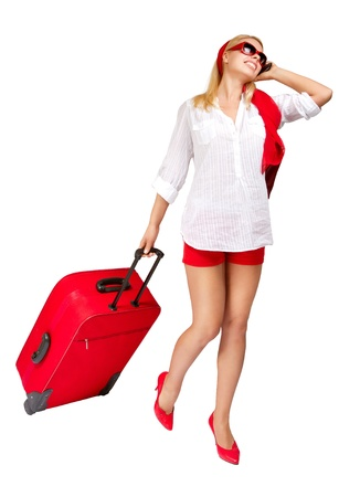 Sexy woman  pulling vacation suitcase talking on phone. Isolated on white
