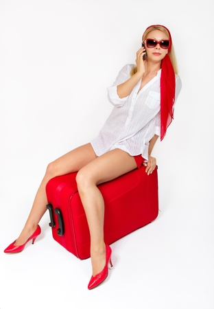 Sexy woman sitting on vacation suitcase talking on phone. White background  photo