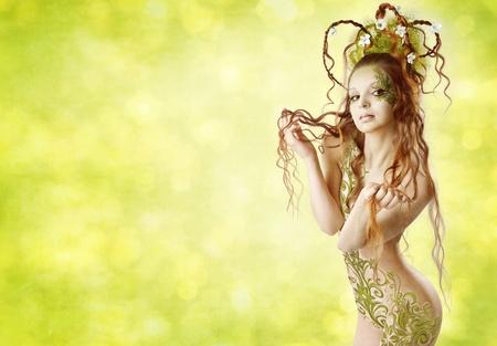 half nude: Beautiful naked woman holding long hair. Spring season. Green bokeh background.