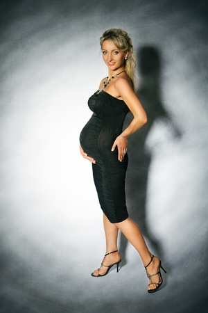 Smiling pregnant woman looking at camera. Luxury cocktail black dress.  Grunge background. photo