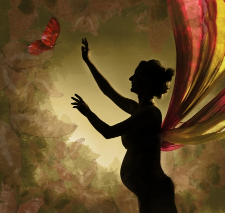 Pregnant woman with wings catching buterfly  photo