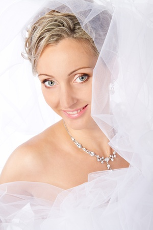 Bride in white veil smiling and looking at camera. Portrait. Fashion wedding shot on a white Stock Photo - 9036575