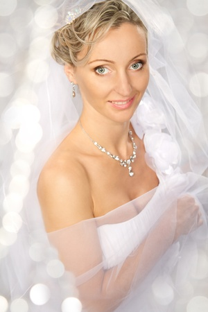 Bride in white veil smiling and looking at camera. White bokeh background. Portrait. Fashion wedding shot on a white Stock Photo - 9036566