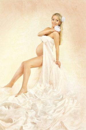 Happy pregnant woman smiling, looking at camera, holding flower. Wavong silk dress, cloth. Art background. photo