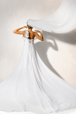 Back of bride in white elegance wedding dress with loop. Long flying veil. Hands raised up. Full length.