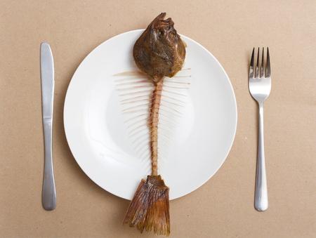 plato de pescado: esqueleto de un pez en un plato. platija comido Foto de archivo