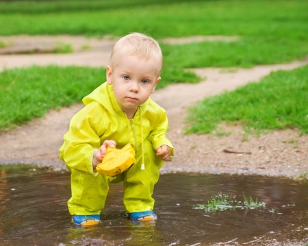 dirty blond: little child playing with ship in the puddle outdoor. Spring season Stock Photo