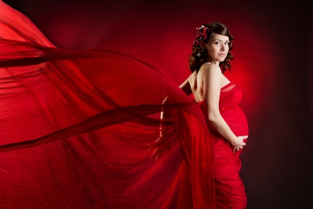 Pregnant woman in red waving dress. Looking at camera. photo