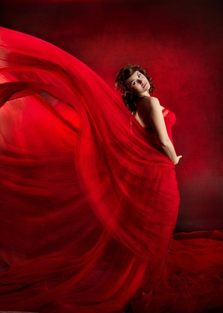 Beautiful woman in red waving flying dress. Looking at camera. photo