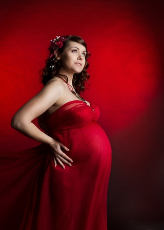Pregnant woman in red chiffon dress. Looking up. photo