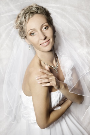 Bride in white veil looking at camera and smiling. Portrait. Fashion wedding shot. photo