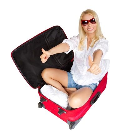 legs open: Woman showing thumbs up, sitting in travel red suitcase. Packed for vacation in summer resort. Isolated over white. Stock Photo