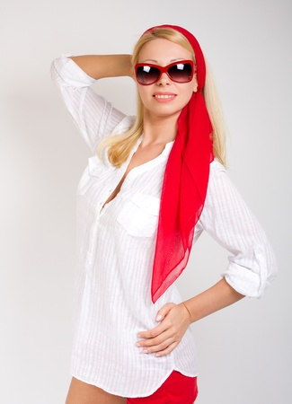 Fashion portrait of sexy woman wearing sunglasses in red scarf around head photo