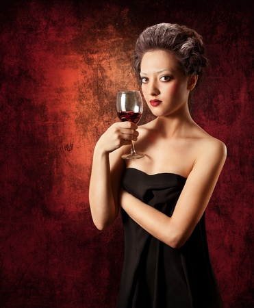 Beautiful woman with glass of red wine on grunge background. Looking at camera. Low key Stock Photo - 9598799