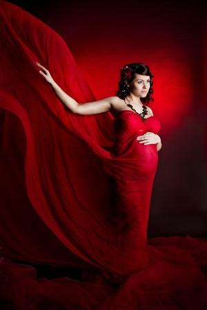 Pregnant woman in red waving flying dress. Lookingforward. Stock Photo - 9598825