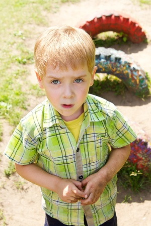 unhygienic: Child with dirty face and hands outdoor at playground. Alone and sad. Summer spring season. Unhygienic conditions Stock Photo