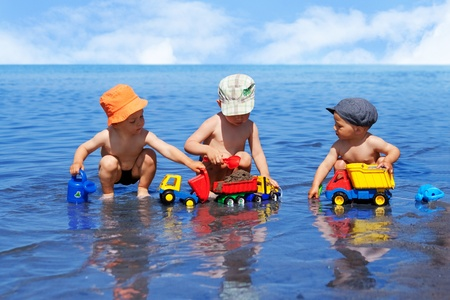 squatting down: Three boys playing on the beach in the water with colorful toy cars