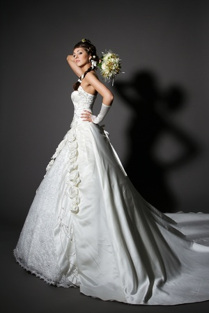 Bride in white elegance wedding dress with tail. Hand rised up with bouquet. Full length. photo