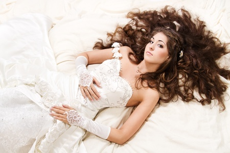 Bride with curly long hair lying over white. High angle view. Fashion wedding shoot. Stock Photo - 10419544