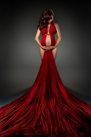 Attractive woman in red waving dress looking down. Naked belly and hips. Over dark background