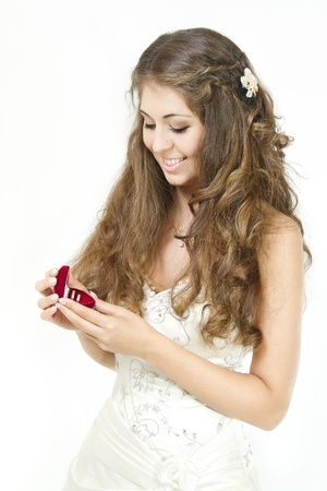 Bride holding red heart shaped box with two golden wedding rings. Smiling and looking at rings. Over white photo