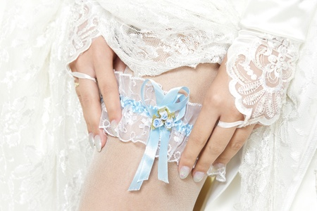 garter: Bride putting a garter with blue ribbon on her leg. Close up.