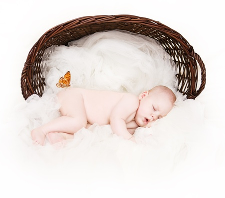 nude baby: Newborn baby sleeping inside of wicker basket over white soft cloth as background. Orange butterfly sitting at the hip. Over white. Stock Photo
