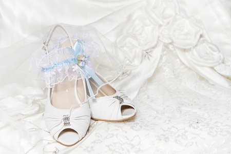 wedding accessories: Brides shoes garter, with blue ribbon, wedding dress. Closeup of wedding accessories. Stock Photo