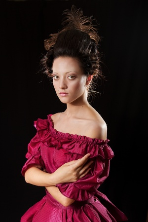 Stylized baroque portrait of beautiful brunette woman in historical costume with crinoline. Low key photo