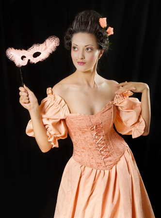 Stylized rococo portrait of beautiful brunette woman in historical costume with crinoline and mask. Low key photo
