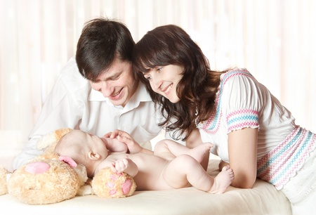 mom and dad: Young smiling parents looking at baby, play with child. Indoor.