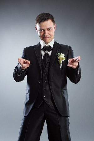 Handsome man in black suit pointing fingers in front of himself. Indicate forward. Grey background. Stock Photo - 10504869
