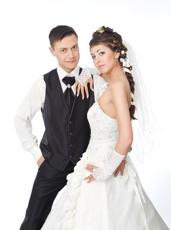 bride and groom background: Beautiful bride and groom standing at white background. Wedding couple fashion shoot.