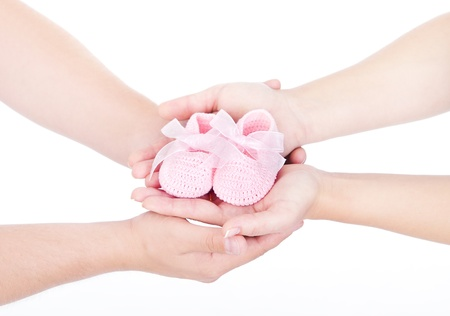 Mothers and fathers hands holding pink newborn baby booties. Over white. Hand in hand.  photo