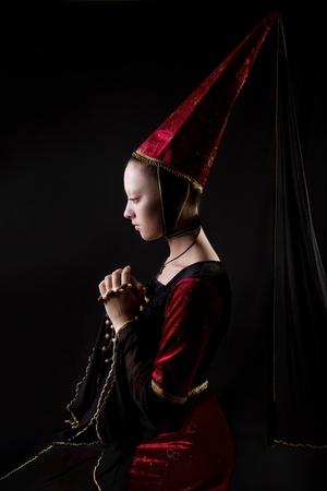 vestidos de epoca: Retrato estilizado estilo medieval de una mujer hermosa en traje histórico. bajo llave. Mirando hacia abajo. Etapa componen Foto de archivo