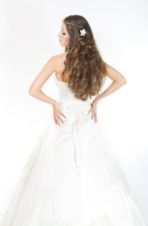 Long curly hair. Bride with hairstyle in wedding dress. Back view. Over white photo