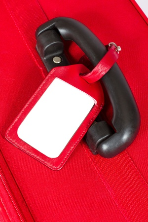 Red suitcase with blank identification tag over white. Closeup. photo