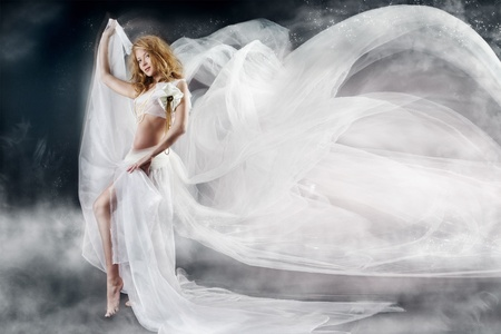looking away from camera: Beautiful woman walking with flying white chiffon fabric, waving  as wings on a wind flow. Mysterious fantasy background