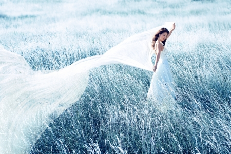 wind dress: beautiful bride in blue field with long waving fabric Stock Photo