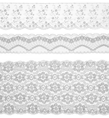 edging: Lace trims ribbon over white. Set of embroidered fabric. Closeup