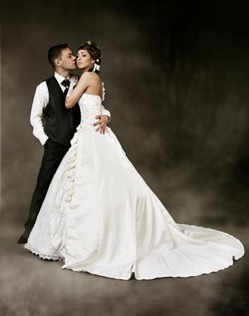 feleségül: Menyasszony és a vőlegény sötét, titokzatos háttérben. Esküvői pár divat lőni. Stock fotó
