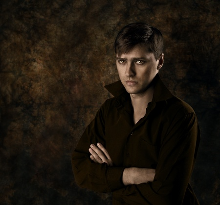 Handsome man sitting over dark brown gothic background with crossed hands. Seriously looking at camera. photo