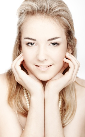 Beautiful girl with clean skin touching face. Closeup over white background Stock Photo - 10922549