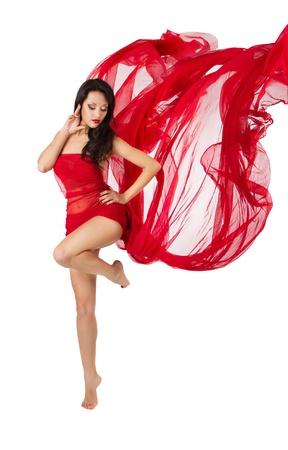 pies descalzos: Mujer bailando en rojo vuelo agitando las alas vestido de gasa en un flujo de viento. Sobre fondo blanco Foto de archivo