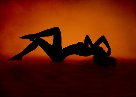 femme nu sexy: Nue silhouette de femme sexy couch�e au rouge sur fond orange