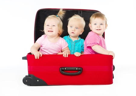 group of three children sitting inside big red suitcase ower white background photo
