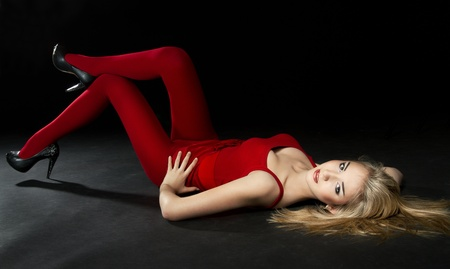 Woman in red tights and clothing lying down over dark background. Perfect body shape. Stock Photo - 11095918