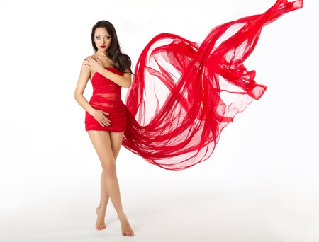 Woman in red flying waving dress as wings on a wind flow. Over white background photo