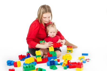 Mother and daughter playing together building blocks over white photo